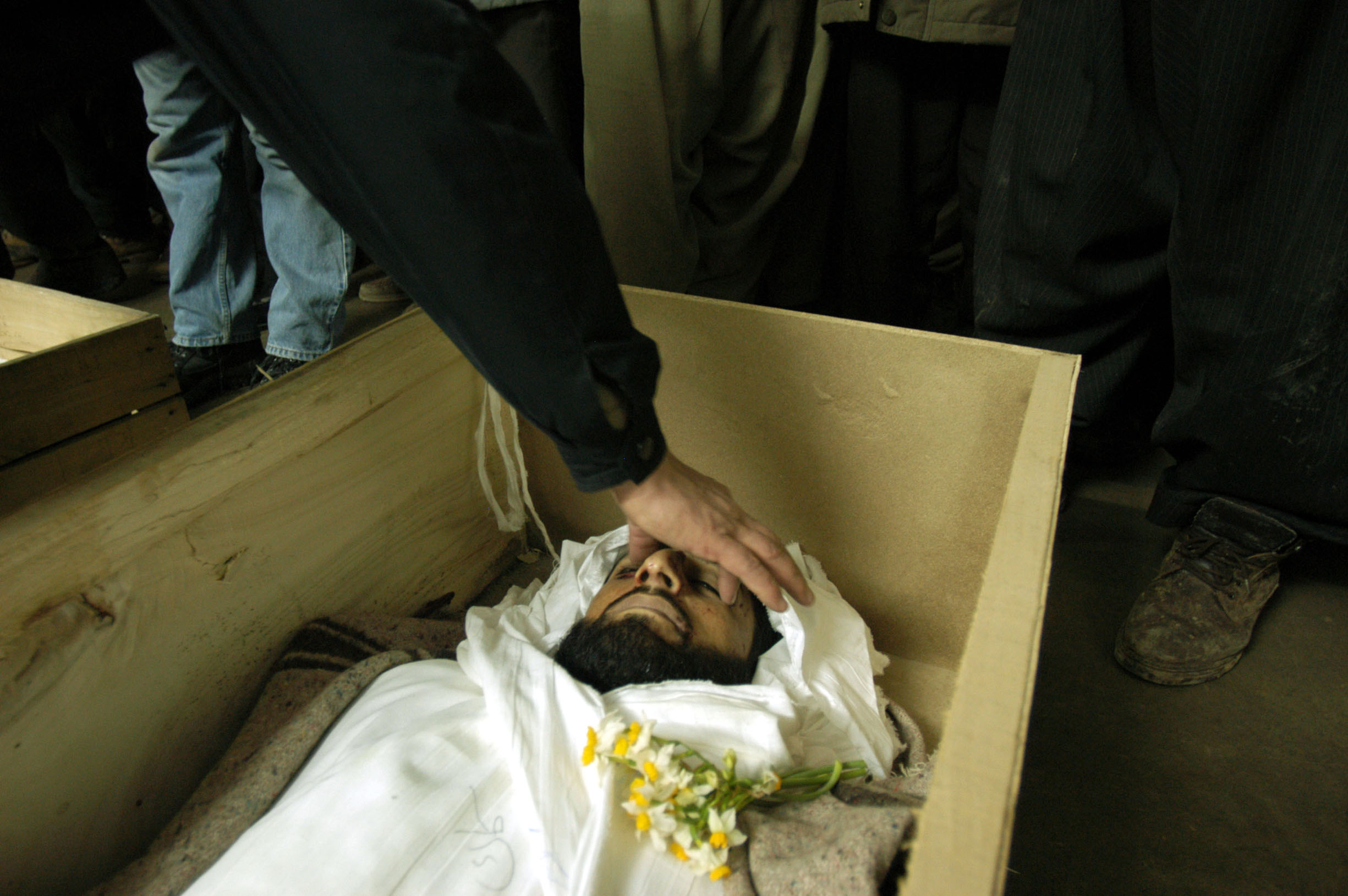 A relative closes the eyelids during the funeral of one of the men killed in a shoot out at a PUK checkpoint in Suleimaniya, Northern Iraq March 5, 2003.  The five men had long beards, and were accused of being Ansar fundamentalists.