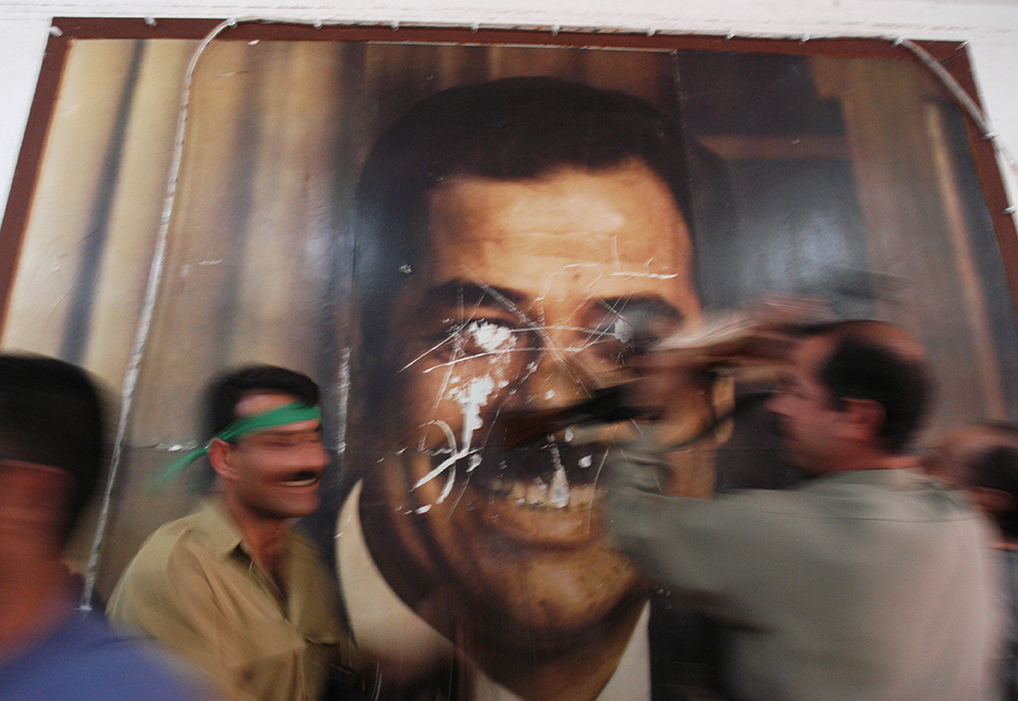 Kurdish Peshmerga soldiers deface a poster of former Iraqi leader Saddam Hussain's poster in the Kirkuk Governate building in Kirkuk hours after it fell from Iraq Central Government rule, April 10, 2003.  Roughly twenty days after the start of the US-lead war on the regime of former Iraq leader Saddam Hussain, cities are falling out of his control, and locals celebrate and destroy statues and symbols of Hussains power.