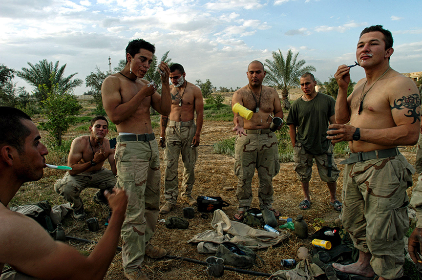 United States Marines take a break to shave in front of one of Saddam Hussain's presidential palaces the day Tikrit fell from Republican Guard rule in Iraq, April 15, 2003.  As the regime of Saddam Hussain fell across Iraq, proof of the many suspicions of how Saddam HUssain concealed his weapons comes to light.