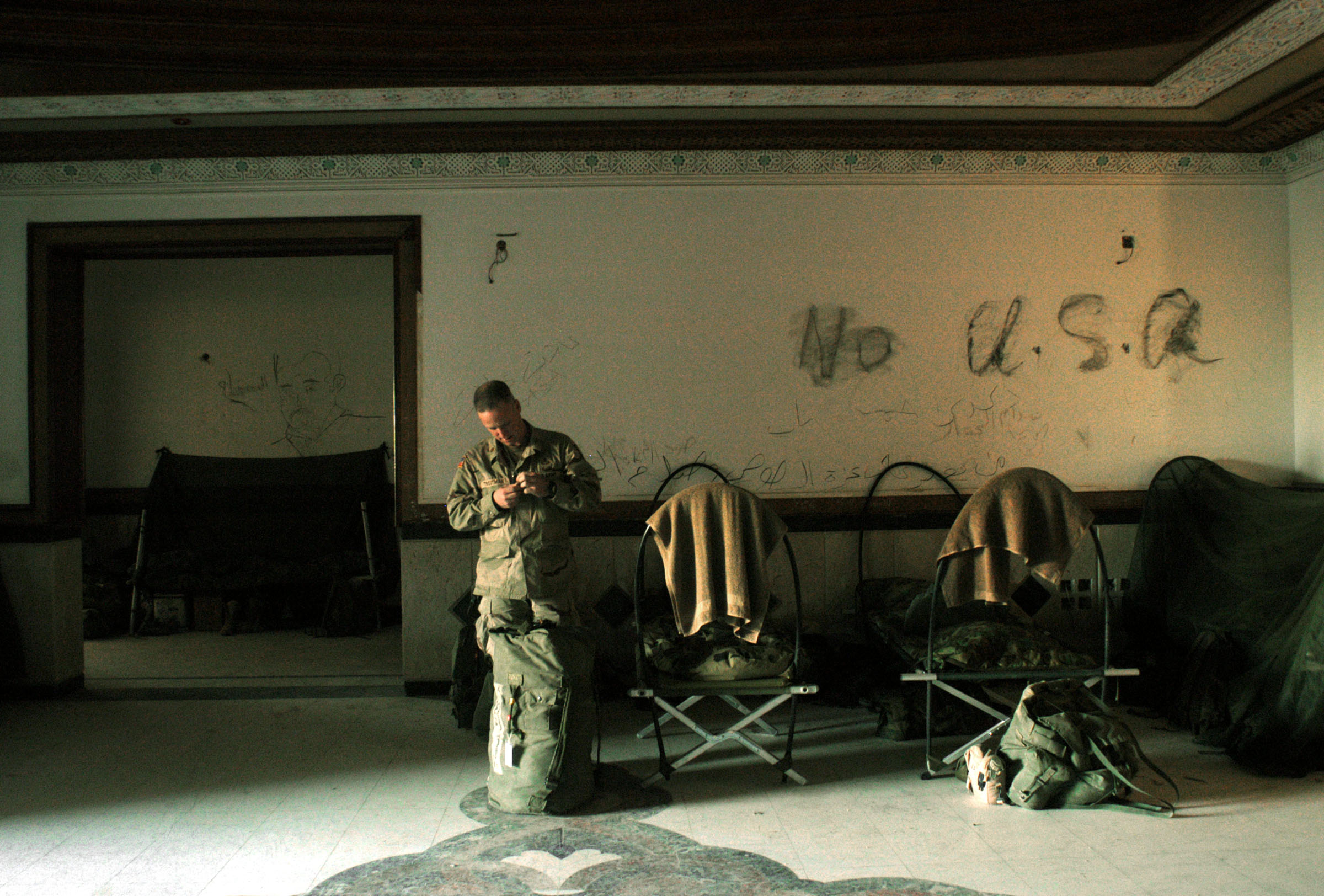 A soldier with the United States 101st Airbourne Division stands in front of Anti-American slogans drawn on the wall of the Division Main Headquarters in one of Saddam Hussain's former palaces in Mosel, Northern Iraq, May 1, 2003.  The palace was Hussain's Northernmost palace in Iraq, and was his VIP palace, and now runs the entire northwest region of Iraq for the 101st Airbourne.