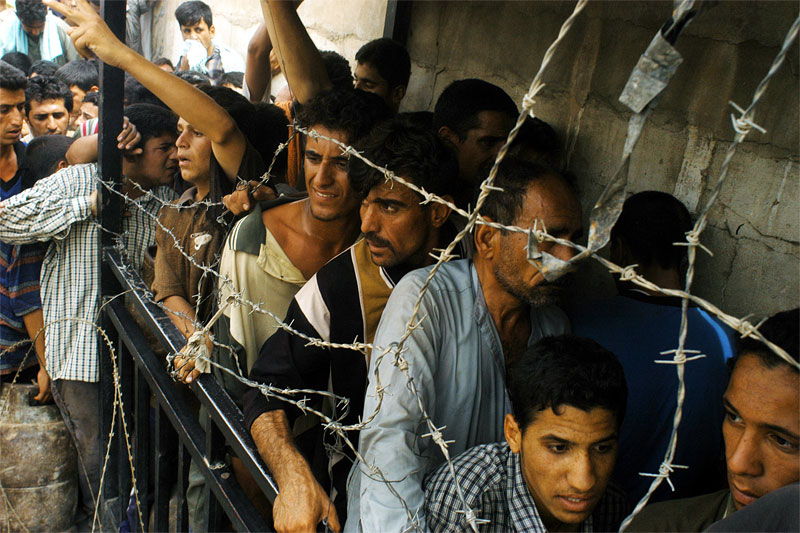 Iraqi men wait on line during a propane gas distribution  in Sadr City, Bagdad, as a crowd of thousands of Iraqi civilians pushing to get aid grows more and more unruly in Iraq, May 28, 2003.  Sadr City is considered the most dangerous, anti-American places in Bagdad, and for weeks after the war, Americans were not able to patrol the streets there, nor hand out aid, water, or gas to the people because it would compromise their safety.
