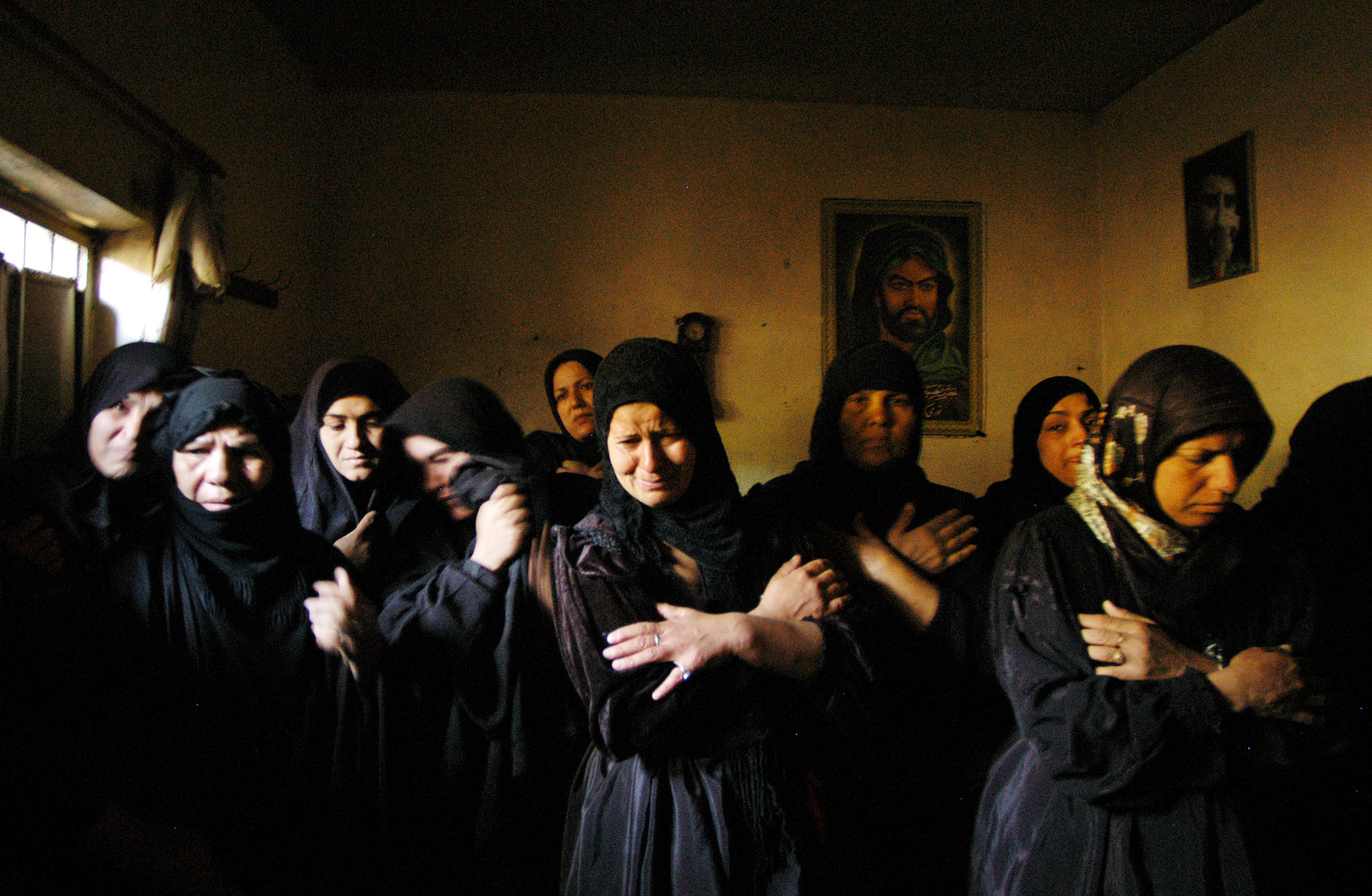 Relatives of Salman Nama Naser, 63, mourn his death at their home in Sadr City, following a day of battle between followers of Iraqi Shiite followers of Muqtada Al Sadr and coalition forces, April 5, 2004.  Dozens of Iraqis have died, as well as at least 9 coalition troops in nationwide fighting across Iraq.