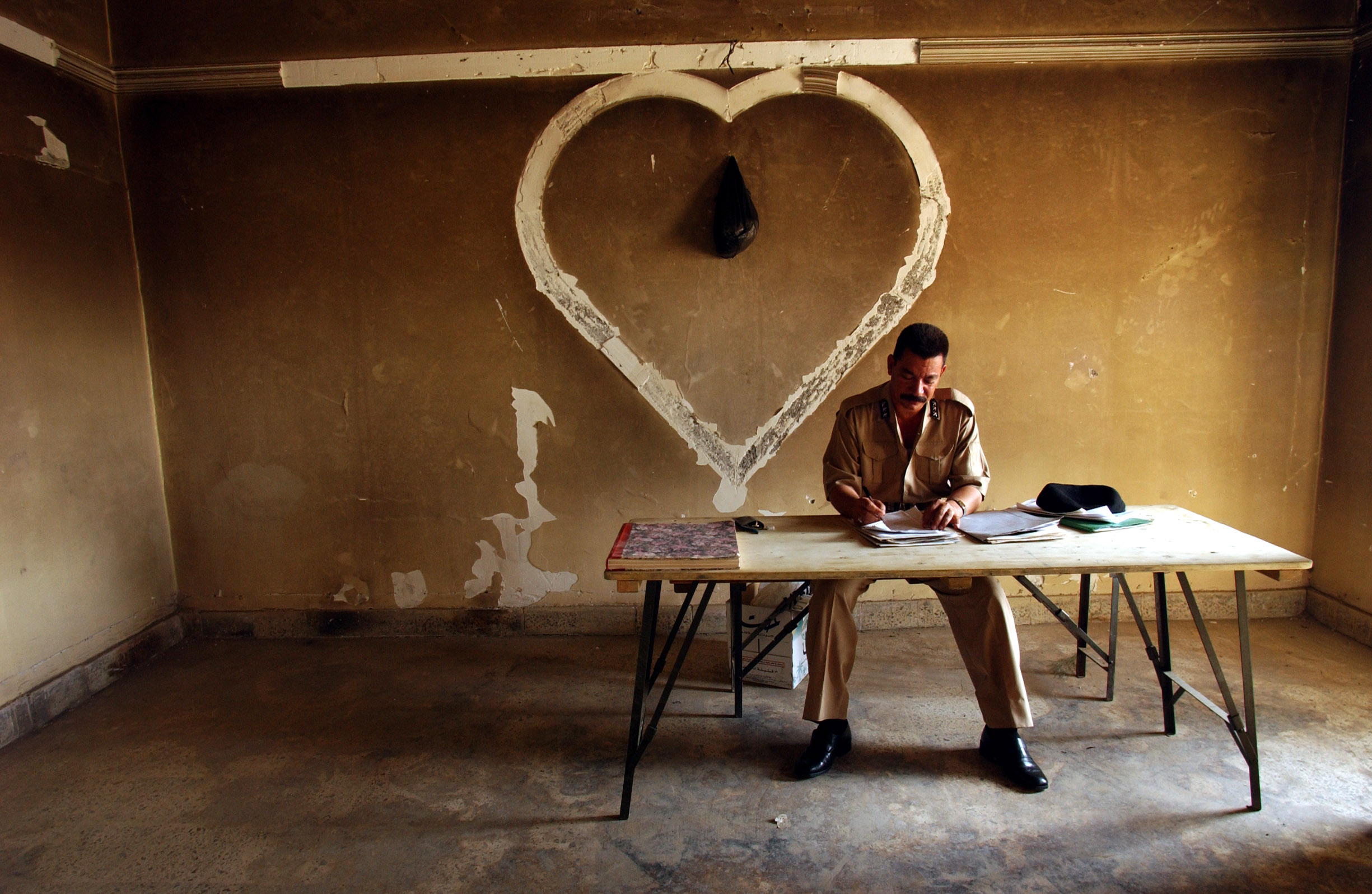 An Iraqi police clerk fills out a report in the former office of the head of the Republic Party of Basra in one of the old Bath Party Headquarters-turned-police station in Old Basra, Iraq, May 26, 2003.  As part of the philospphy of the Royal MIlitary Police, the soldiers are teaching Iraqi Policemen to fill out reports for all everything that happens in their jurisdiction, in an effort to eventually pass all responsibility on to the Iraqis.  There is rising speculation as to whether the British manner of patrolling Basra has been more successful in governing the city in contrast to the American's more stand-off-ish approach to governing Bagdad.  Unlike the Americans in Bagdad, the British often patrol Basra with no body armour and no helmets, and sometimes go out without their automatic weapons.