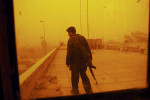 An Iraqi Policeman stands guard on a roof in a sandstorm at the Baghdad Academy for Police officers in Iraq, February 15, 2004.   Iraqi police have suffered grave losses this week with two major attacks on police stations and recruits to be officers, calling into question whether Iraq is ready for the transfer of power to Iraqi officials.