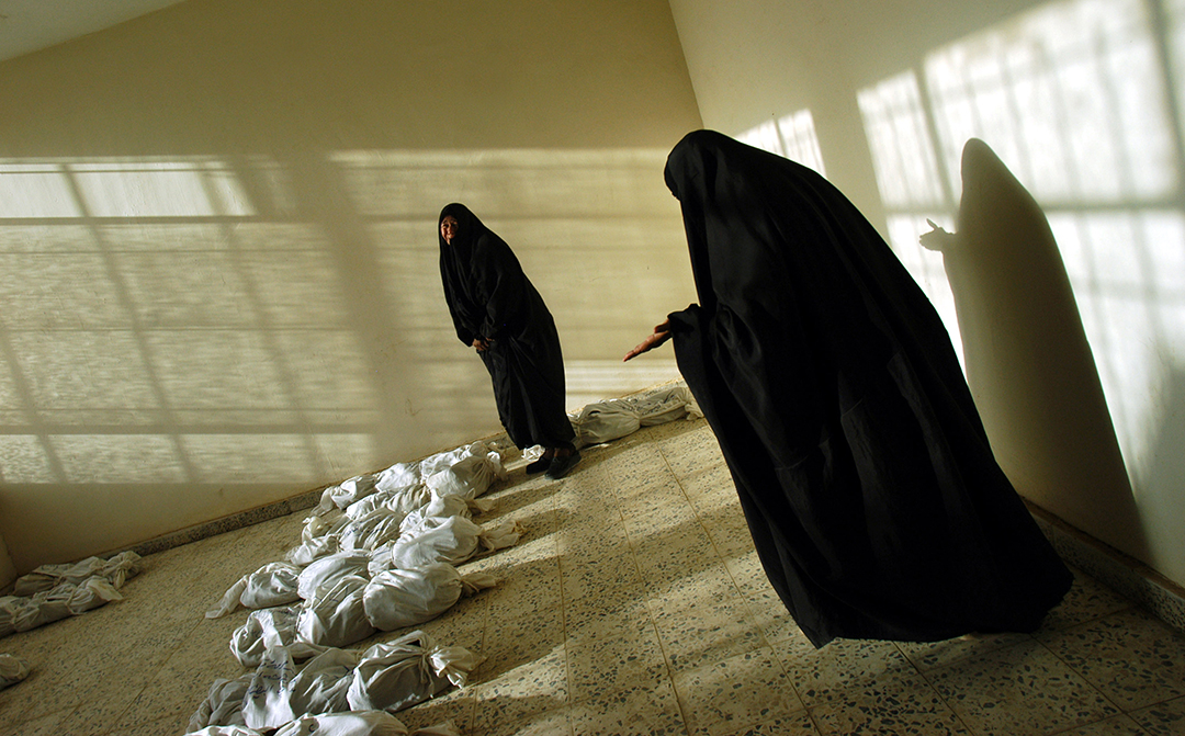 Iraqi women weep as they walk along rows of remains of bodies, some looking for loved ones, discovered  in a mass grave South of Bagdad, and lied out in a building in Iraq, May 29, 2003.  Since the fall of Saddam Hussain's regime in Iraq, thousands of bodies have been pulled from mass grave sites around the country, evidence of the brutal, bloody regime of the former dictator.