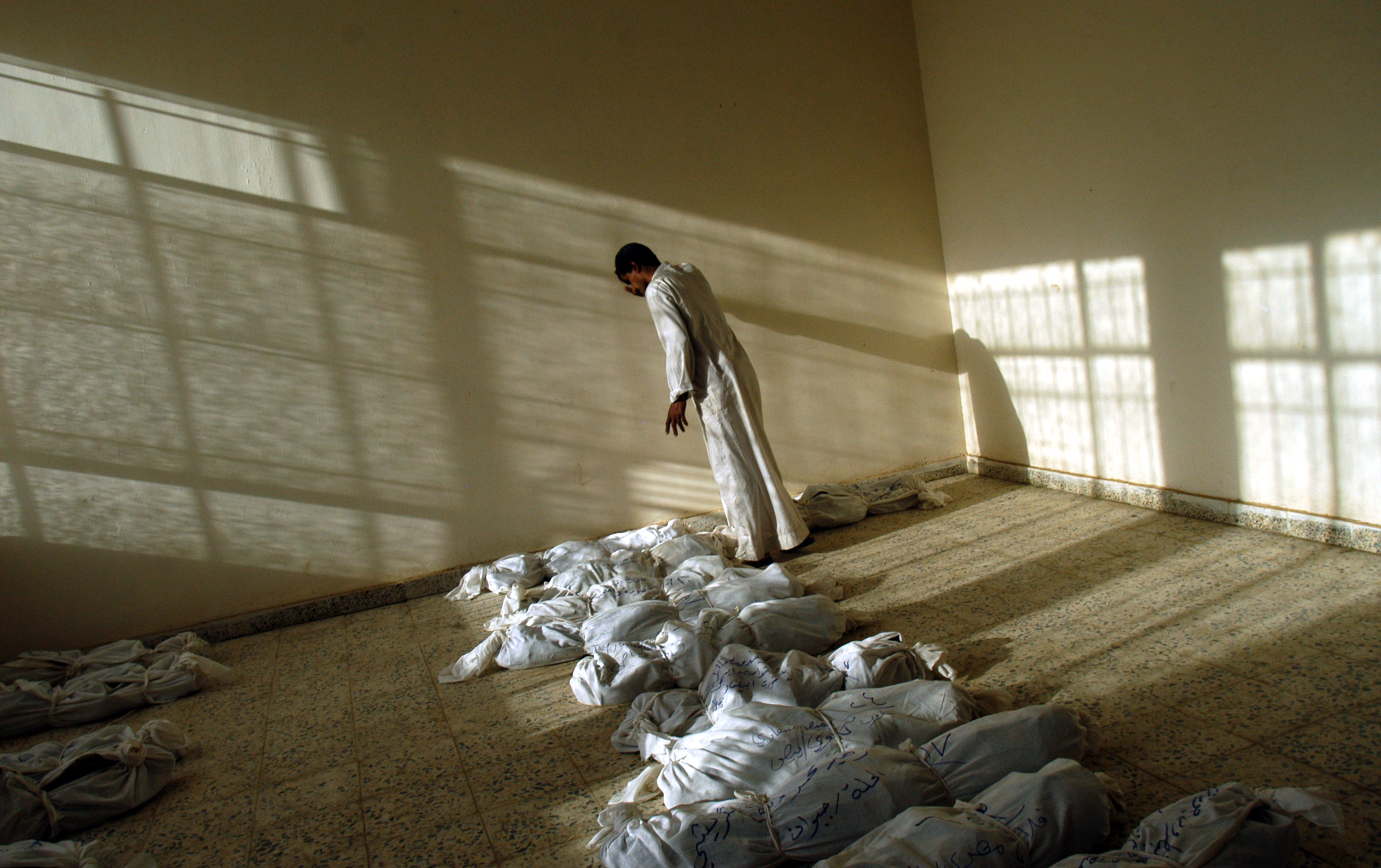 An Iraqi man leans against the wall as he walks along rows of remains of bodies discovered  in a mass grave South of Bagdad, and lied out in a building in Iraq, May 29, 2003.  Since the fall of Saddam Hussain's regime in Iraq, thousands of bodies have been pulled from mass grave sites around the country, evidence of the brutal, bloody regime of the former dictator.