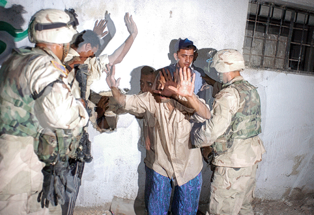 United States soldiers with the 82nd Airborne, 2nd Battalion guard men they have detained for carrying weapons and driving while intoxicated during a night patrol in Bagdad, Iraq, May 15, 2003.  Soldiers throughout Bagdad are working with Iraqi Police officers to help maintain order and get Iraqi officers back on the street.   Since the fall of the regime lead by former Iraqi leader, Saddam Hussain, Bagdad has seen high crime rates and major shortages in Petroleum, electricity, and water.