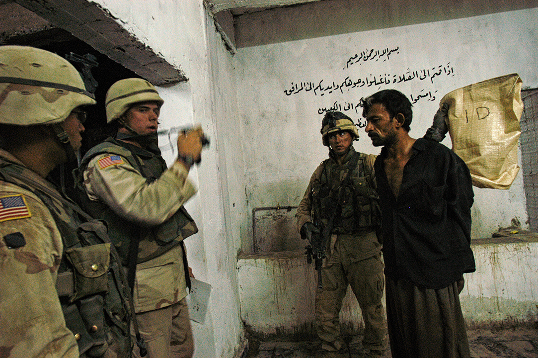 Soldiers with the 4th ID, 3rd Brigade, from the 1st Batallian-68th Armored Regiment detain an Iraqi found on a compound American intelligence indicated belonged to members of the Bathist party and supporters of former Iraqi leader Saddam Hussain in the early hours of the morning roughly 30 km North of Baghdad near Balad, June 29, 2003.   US troops acted as part of a massive, across the 4th infantry division series of night raids and patrols that took place in the early morning hours of the 29th as a way of showing their force and retalliating against the recent spate of attacks against US troops throughout Iraq.   The area of the raids encompassed the area north of Baghdad as far as a bit past Tikrit, along the Tigris, where there are presumed to be Bathist strongholds, and deep-roted support for former Iraqi leader Saddam Hussain.