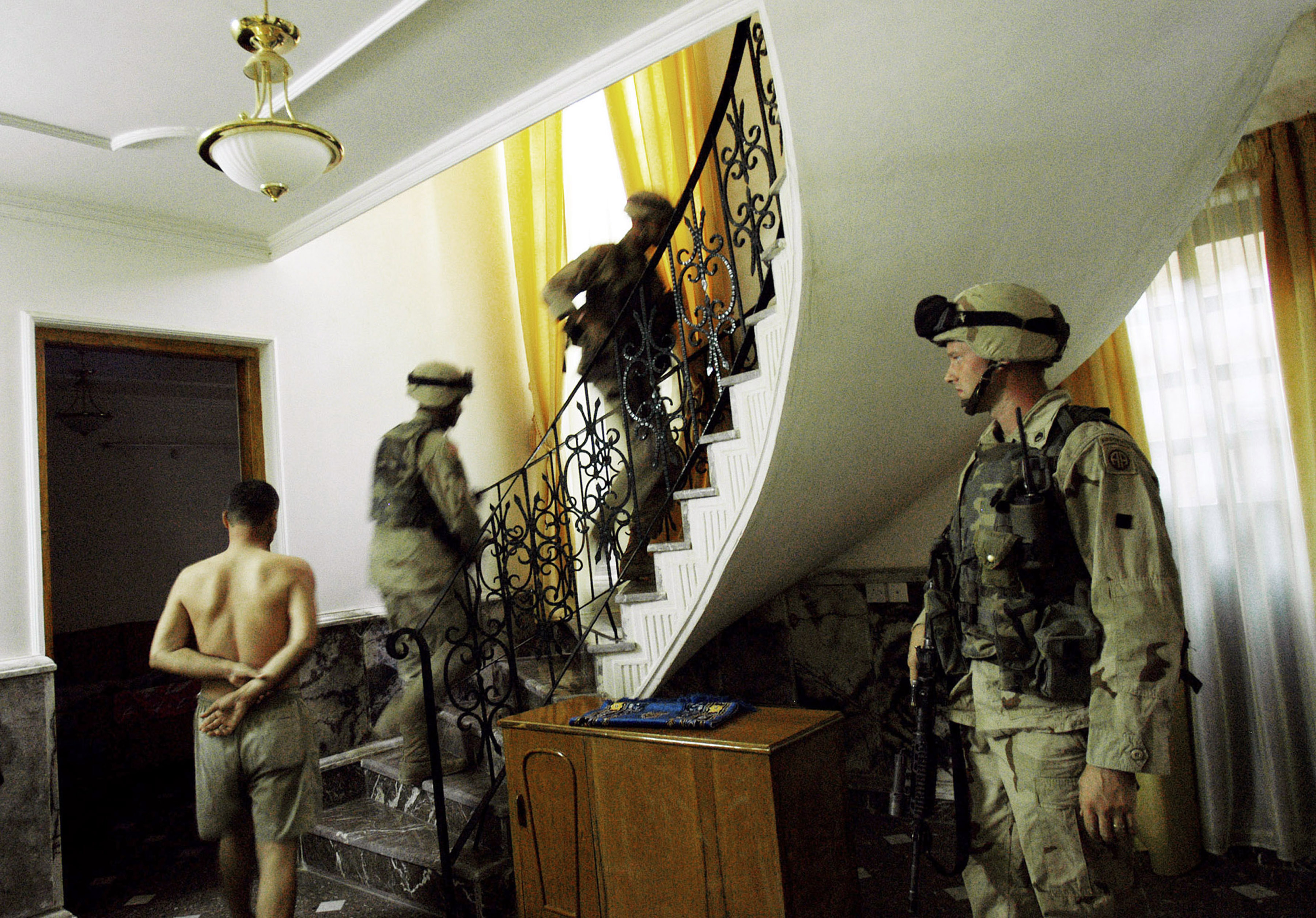 Soldiers from the 82 Airborne Division, 2nd Brigade, walk through a house in the Aldora section of Baghdad during an early morning  house to house search for weapons in Baghdad City, Iraq, June 22, 2003.  In an effort to reduce crime throughout Baghdad, US Troops have implemented a one-weapon rule for Baghdad locals, whereby they are allowed one pistol or Kalashnikov either in their homes or offices, and no automatic weapons.