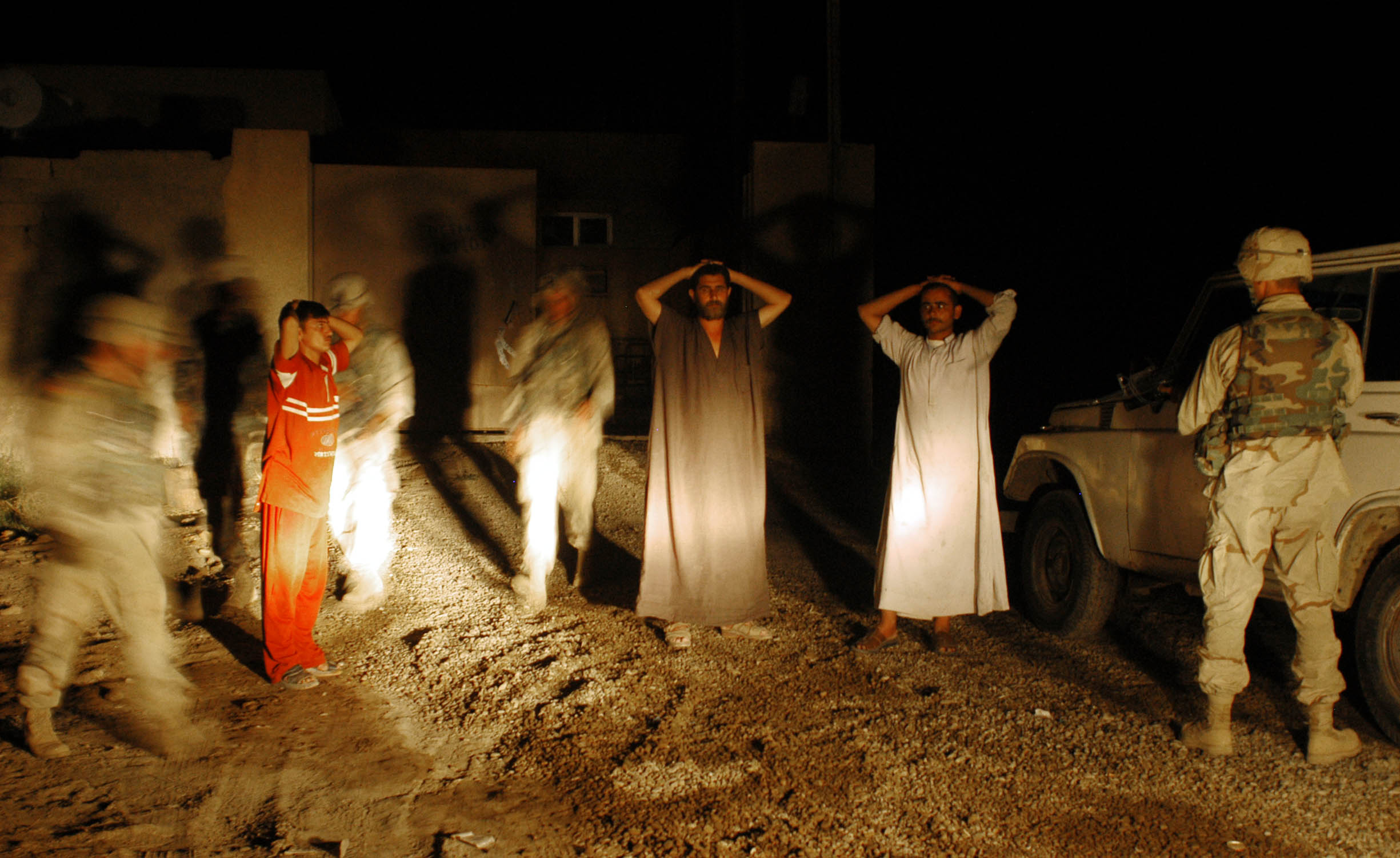 Soldiers with the 4th ID, 3rd Brigade, from the 1st Batallian-68th Armored Regiment momentarily detain and search Iraqi men during a night patrol north of Baghdad near the Balad Base in Iraq, June 27, 2003.  Minutes after this image was shot, an Iraqi civilian crossed over what was possibly a remote detonated explosive device set in the road intended for the US troops meters before the convoy of US vehicles, and severlely injured the man.   In recent weeks, United States troops have suffered hundreds of attacks by Iraqi throughout Iraq, and are stepping up offensive operations throughout the country in search of opponents to US occupation of Iraq.