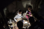 An Iraqi Yazidi family eats dinner by the light of a lantern at the Bahjad Kandal camp near the Iraqi border with Syria, in Northern Iraq, August 16, 2014. Since IS started making its way across Iraq, and overrunning various towns, hundreds of thousands of Iraqis have been displaced across the country. The American military is helping fight IS with targeted airstrikes on IS positions, and Peshmerga are fighting on the ground.