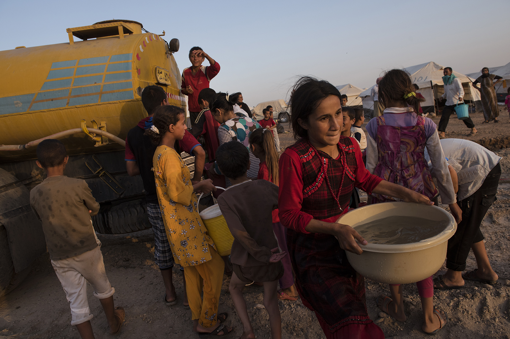 Iraqi Yazidi families fight to take water from a government water truck at the Bajid Kandal camp near the Iraqi border with Syria, in Northern Iraq, August 17, 2014. Since fighters with the Islamic State started making its way across Iraq, and overrunning various towns, hundreds of thousands of Iraqis have been displaced across the country. The American military is helping fight IS with targeted airstrikes on IS positions, and Peshmerga are fighting on the ground.