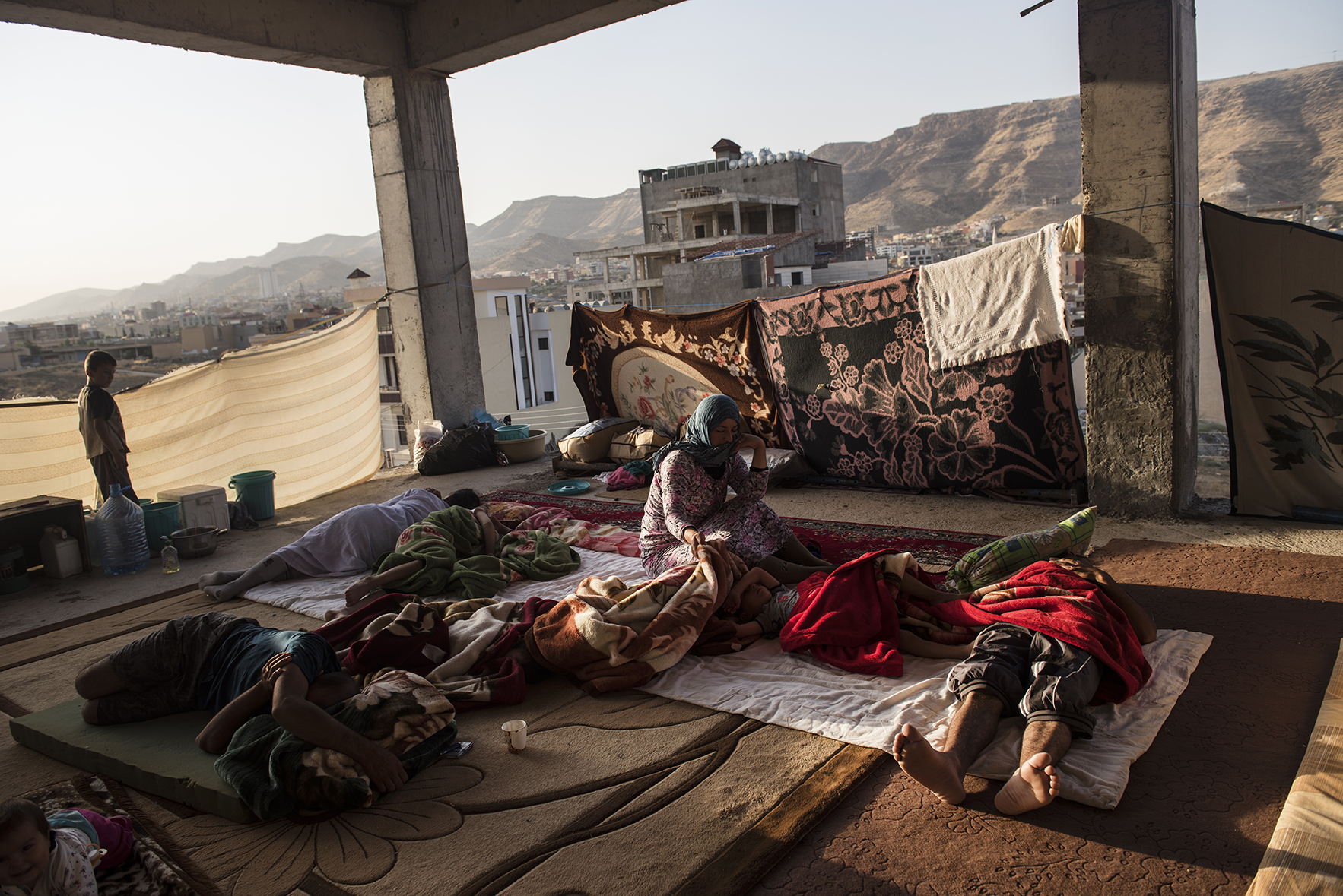 Iraqi Yazidi families live in partially constructed buildings in Dohuk, in Northern Iraq, August 17, 2014.  Since fighters with the Islamic State started pushing through Iraq and murdering and terrorizing thousands of civilians, thousands have been displaced from their homes across the country.  The United Nations is beginning its largest humanitarian aid distribution in a decade.