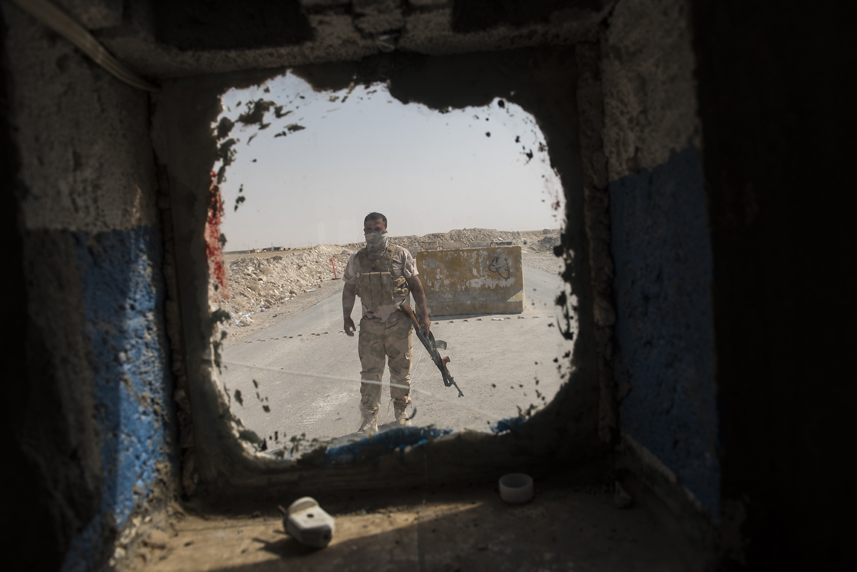 A Kurdish stands guard at a checkpoint  at the edge of the largely abandoned frontline village of Mahmur, where fighters with the Islamic State are estimated by the local Peshmega commander to be as close as 3 miles away, in Northern Iraq, August 15, 2014. Since IS started making its way across Iraq, and overrunning various towns, hundreds of thousands of Iraqis have been displaced across the country. Mahmur fell to the Islamic State less than two weeks prior, and after the aid of American air strikes, is now back in the hands of the Peshmerga.  Most civilians are gone, and those who remain are vigilant for the potential return of IS fighters at any moment. civilian population is all but gone.