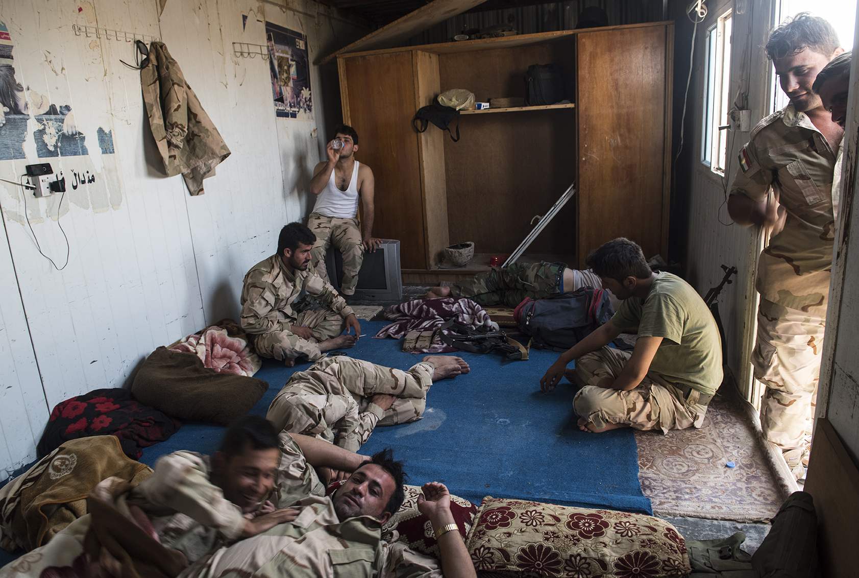 Kurdish Peshmerga fighters sleep after standing guard the previous night at a checkpoint in the largely abandoned frontline village of Mahmur, where fighters with the Islamic State are estimated by the local Peshmega commander to be as close as 3 miles away, in Northern Iraq, August 15, 2014. Since IS started making its way across Iraq, and overrunning various towns, hundreds of thousands of Iraqis have been displaced across the country. Mahmur fell to the Islamic State less than two weeks prior, and after the aid of American air strikes, is now back in the hands of the Peshmerga.  Most civilians are gone, and those who remain are vigilant for the potential return of IS fighters at any moment. civilian population is all but gone.