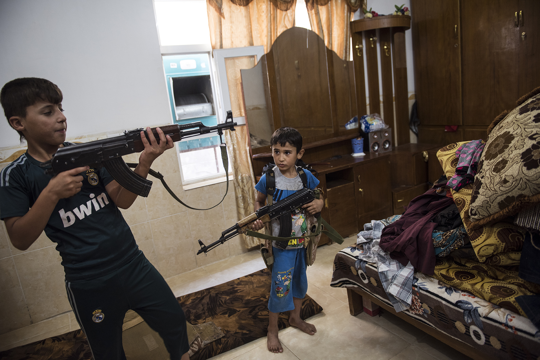 Saleh, 13, and his brother, Bakhtiar, 6, play with the guns and protective gear their father has prepared in case fighters with the Islamic State return to their frontline town of Mahmur, in Northern Iraq, August 15, 2014. Both boys have been taught how to shoot in case they need to help defend the family.   Since IS started making its way across Iraq, and overrunning various towns, hundreds of thousands of Iraqis have been displaced across the country. Mahmur fell to the Islamic State less than two weeks prior, and after the aid of American air strikes, is now back in the hands of the Peshmerga.  Most civilians are gone, and those who remain are vigilant for the potential return of IS fighters at any moment. civilian population is all but gone.