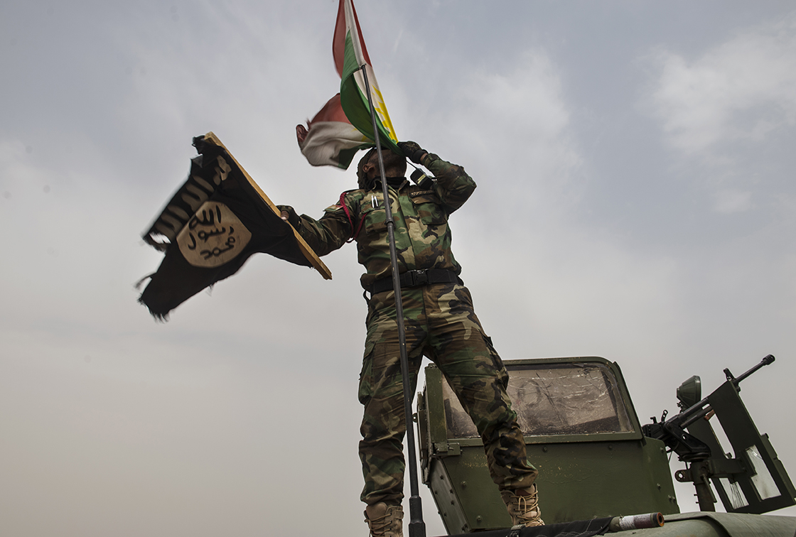 A Kurdish Peshmerga kisses a Kurdish flag as he shows off the Islamic State flag he claimed from a checkpoint as he and other Peshmerga forces celebrate and pose for photographs at the Mosel dam the morning after Peshmerga and Iraqi Special forces defeated fighters with the Islamic State and reclaimed the dam in Northern Iraq, August 19, 2014.  The Peshmerga explained that when he grabbed the flag from a checkpoint, it had been bobby-trapped with explosives, but they failed to detonate. The American military is helping fight IS with targeted airstrikes on IS positions near the Mosul Dam, and Peshmerga and Iraqi Special Forces are fighting on the ground.