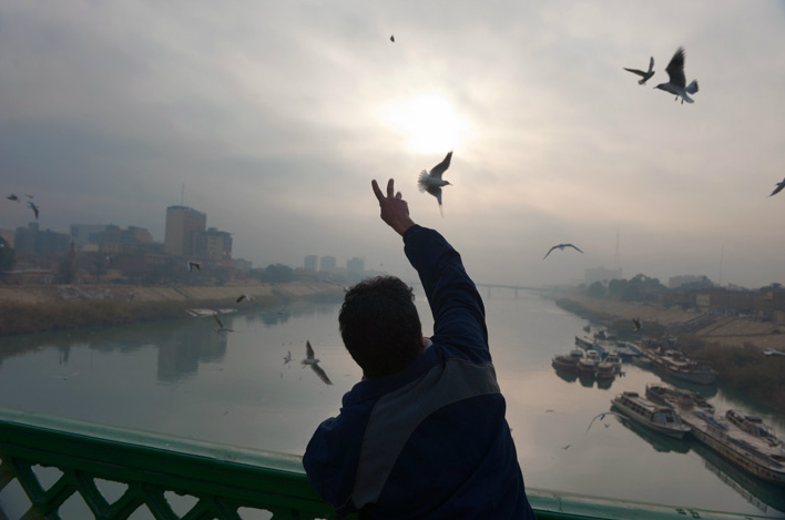 On a bridge over the Tigris a man feeds gulls at dawn as water taxis await the morning's first passengers.