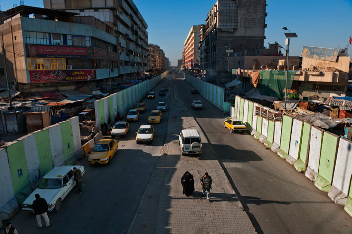 Pedestrians navigate Al Jumhuriyah Street, where 12-foot blast walls shield markets on either side. Shoppers skirt the walls and slip between concrete blocks to enter the animal market (at right) and the Shorjah bazaar (at left), where bomb attacks occurred during the years of sectarian conflict.