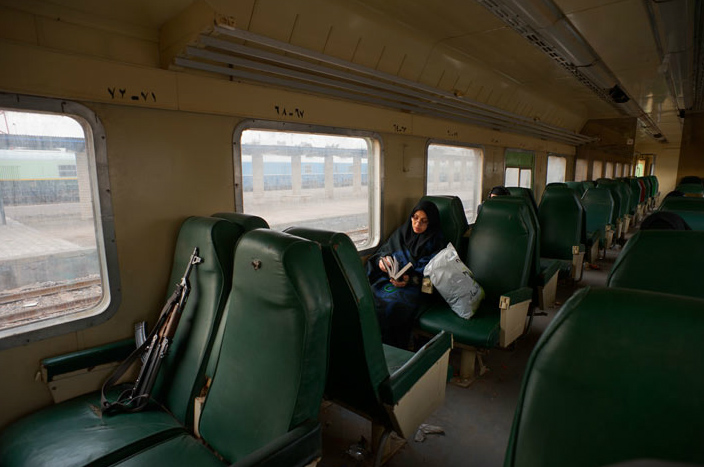 A train passenger traveling from Baghdad to Karbala, a Shiite holy city some 60 miles south of the capital, reads a prayer book. A police officer's rifle rests on the front seat.