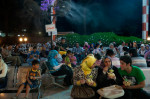 Sitting beneath fans spraying a cool mist, families savor evening snacks at a park in Baghdad's upscale Al Karradah district.