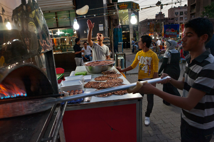 Vendors prepare lahm bi ajeen, similar to pizza, in central Baghdad's bustling, upscale Al Karradah district. Roadside bombs in the neighborhood are a continuing hazard but have not deterred shoppers. Generators help keep lights ablaze during the city's frequent power cuts.