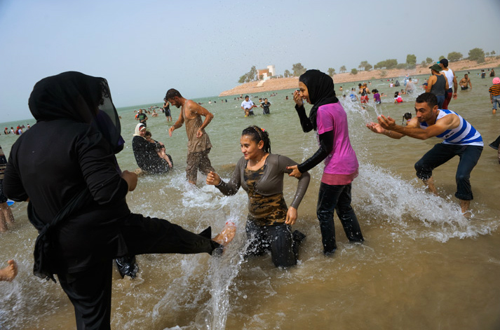 Iraqis escape blistering city temperatures, which can exceed 110°F, in Habbaniyah Lake, 50 miles west of Baghdad. Once a top tourist and honeymoon destination, the Habbaniyah area filled with Sunni refugees fleeing militia violence after the invasion. Tourists have begun trickling back.