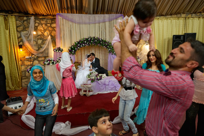 Big weddings costing up to $10,000 have become more common as young people feel safe enough to plan for the future. Some 300 guests celebrated for two days when bride Heelan Muhammad, 23, married Husham Raad, 30, last October. They are saving for a house. Daily life isn't always easy, says 24-year-old Raad Ezat-Khalil (with baby), the groom's cousin and matchmaker, but {quote}the most important thing is how strong and determined people are.{quote}