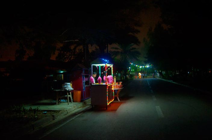 At the end of a long day a cotton candy vendor awaits customers in Zawra Park, home to an amusement park and the city zoo. The park shuts at 11 p.m., an hour before the nightly curfew empties streets and a new day begins.