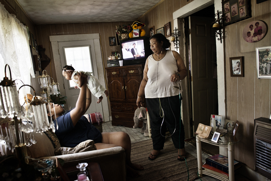 Vonda Wells, 41, stands with her Oxygen supply at home with her daughter, Brandyce Wells, 19, and Brandyce's four month old daughter, Imari, in Clinton, Mississippi, September 29, 2012.  Vonda suffers from Asthma, High Blood Pressure, congestive heart failure, and is a survivor of stage four Hodgkin's disease. she is on Medicaid. Mississippi has some of the highest rates of diabetes, obesity, infant mortality, AIDs, among other ailments, in the country, and though millions of federal funds have been thrown at the problems for years, conditions have only gotten worse.