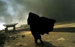 An Iraqi woman walks through a plume of smoke rising from a massive fire at a liquid gas factory as she searches for her husband in the vicinity of the fire in Basra, Iraq, May 26, 2003.  The fire was allegedly started by looters picking through the factory, and residents in the vicinity feared the explosion of the four liquid gas tanks on the premisis.   Weeks after the end of the war, looting continues to be one of the main problems for both Basra and Bagdad cities as coalition forces struggle to get life back to normal.  (Credit: Lynsey Addario/ Corbis Saba)