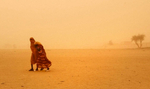 Chadian girls brave a sandstorm in Bahai, Chad, roughly seven kilometers from the Sudan border, August 18, 2004.  Thousands of refugees have streamed out of Sudan into Chad in recent months as fighting persists in Darfour.  (Credit: Lynsey Addario, for The New York Times)
