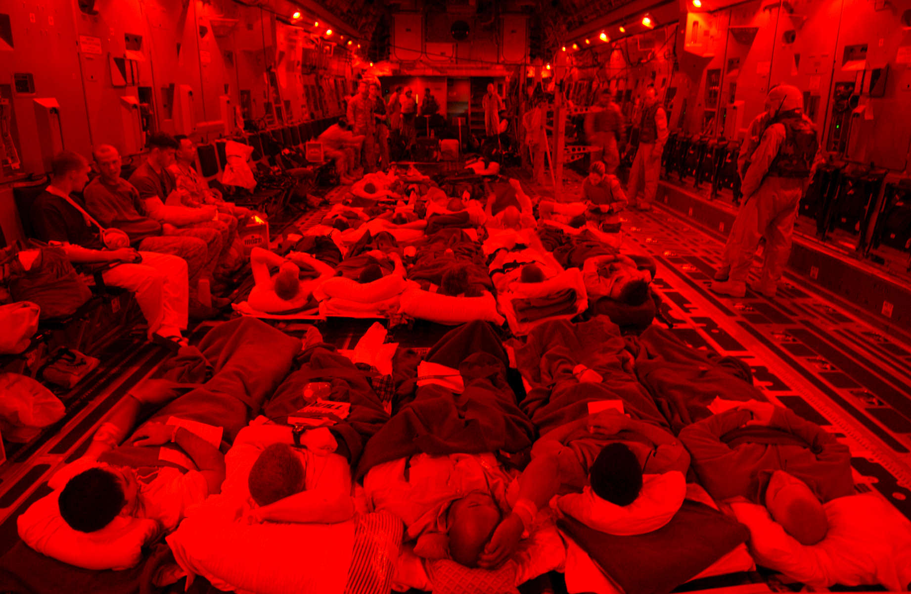 United States injured soldiers sit on a cargo plane before taking off to Germany from the Balad airforce base.  The interior lights of the plane are red because of an 'alarm red' attack, which indicates that the base is under attack, usually by incoming mortar rounds.  Since the attack on Fallujah began in early november, hundreds of soldiers have been injured and evacuated from the country.