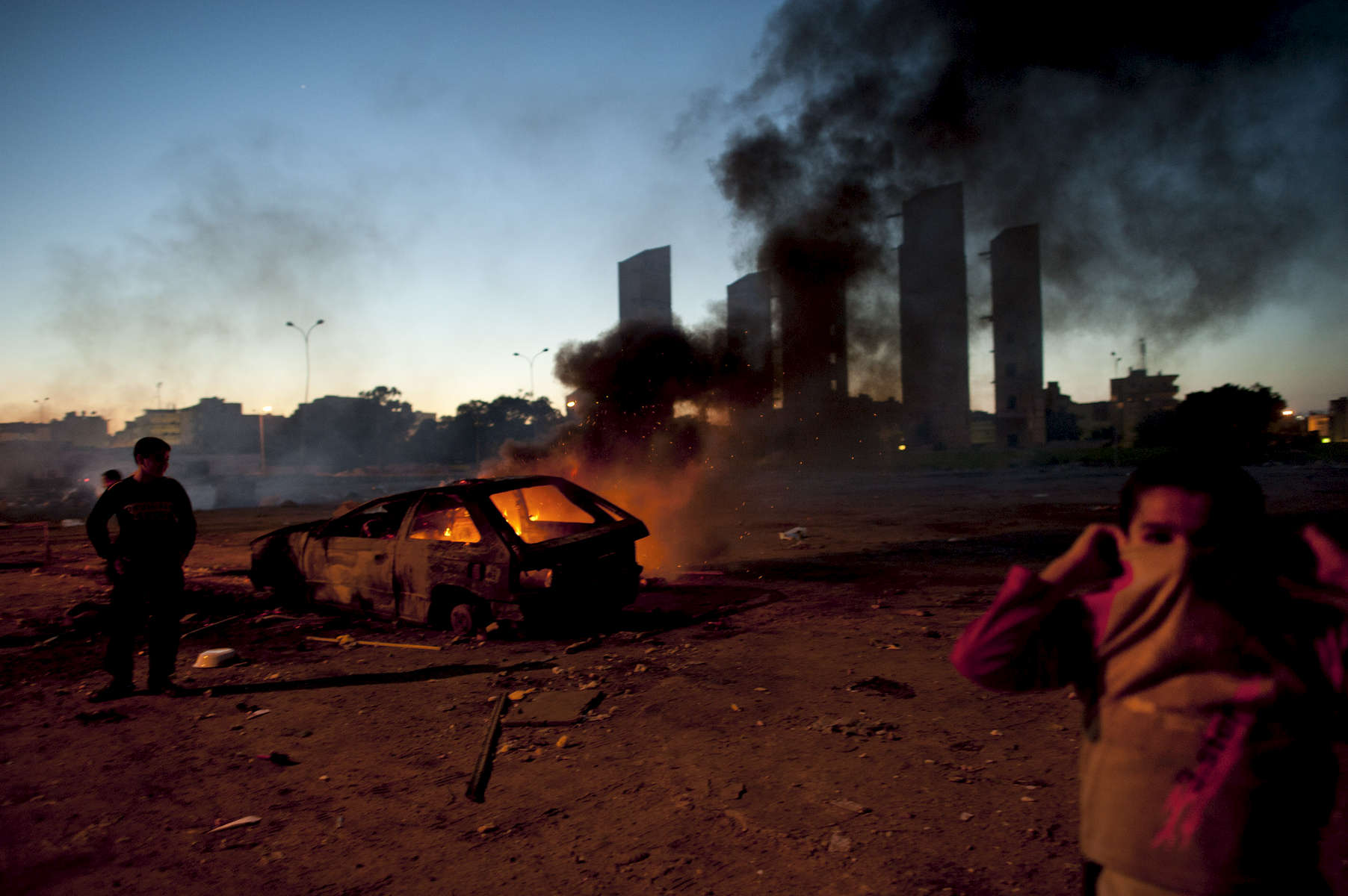 Kids play around a burning car in a residential neighborhood in Benghazi, in Eastern Libya, February 28, 2011. Dangerous confrontations have been going on between opposition forces and those loyal to Col. Qaddafi across Libya.  (Credit: Lynsey Addario for The New York Times)