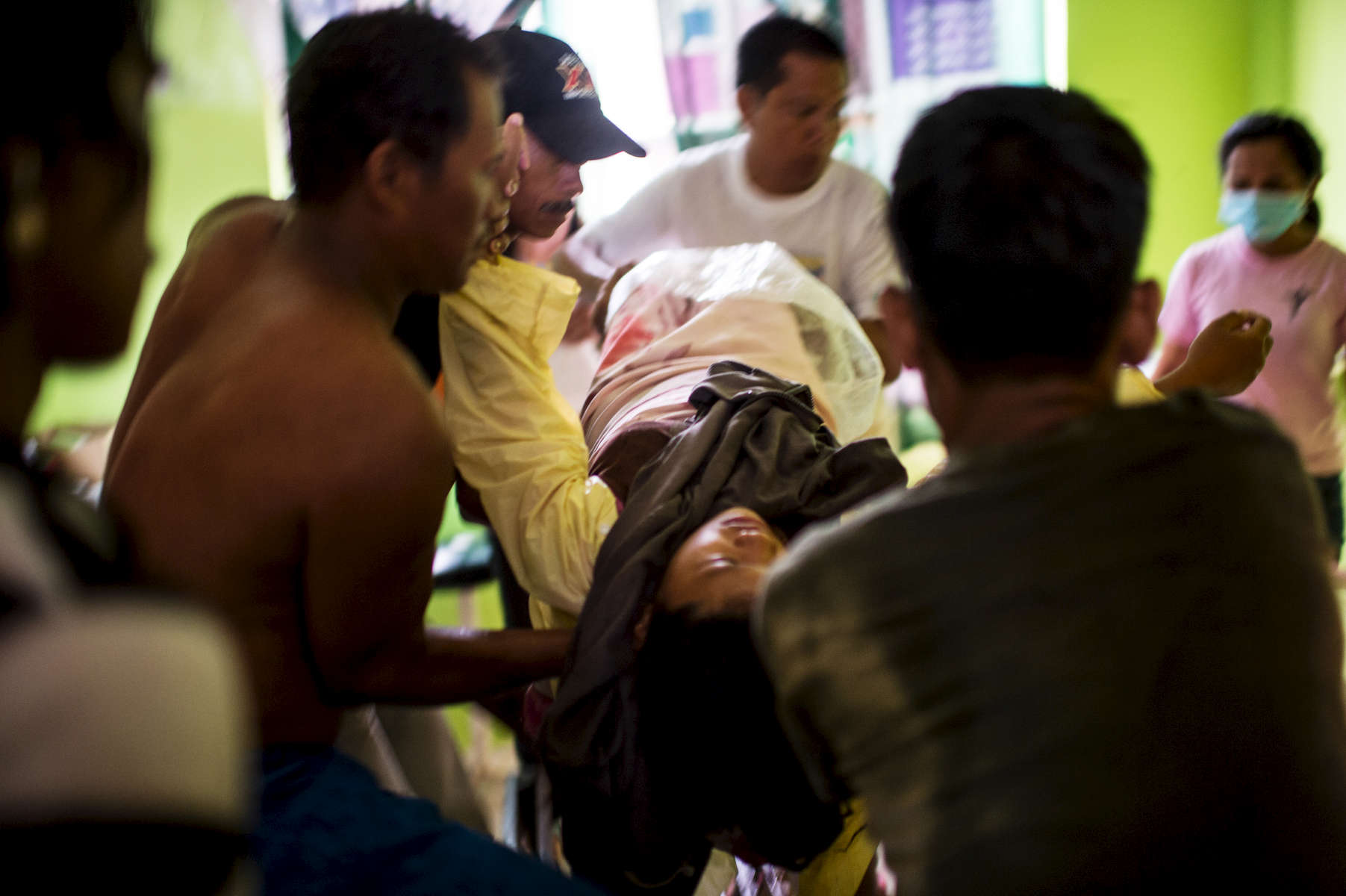 Midwife Norena Malate delivers the baby of Analyn Pleado, 18, as Analyn's husband, Ryan Bacate, 21, looks on on the side of the road en route to the rural health unit in Tolosa, outside of Tacloban, in the Philippines, Januray 11, 2014. During Typhoon Haiyan, the couple's house was destroyed, and they were displaced to a more remote village of Tabon. Analyn feared after the typhoon that she wouldn't find a place to deliver. 'All the clinics and Barangay health stations were destroyed.'  She had gone into labor the evening before, but because it was raining, and dark, she waited until the morning to travel by motorcycle with her husband to the nearest clinic with a midwife in Tolosa.  A stranger passing by witnessed Analyn in labor on the side of the road, and went to bring the midwife.  Typhoon Hayien hit the Philippines on November 8, 2013, and killed some six thousand people, and affected some 14.1 million others, destroying their homes, livelihoods, and displacing families.  There are currently over 250,000 pregnant women in the affected area, with much of the medical infrastructure destroyed. (Credit: Lynsey Addario, for Save the Children)