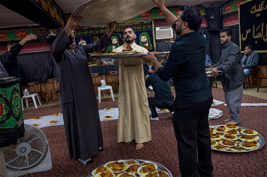 Friends and family in Dearborn, Michigan, hold a traditional martyr's funeral for Ali Qasim al Khafaji, who was fighting with the Iraqi security forces when he was killed in Mosul by Islamic State militants. The attendees prepare to dine on masgouf, or grilled fish, an Iraqi specialty.