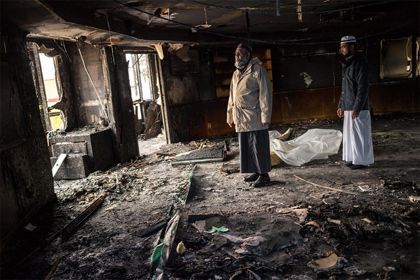 Imam Fazal Hassan and Amjad Shaik survey damage to their mosque in Bellevue, Washington, after it was set on fire last year. A mentally ill man who had earlier assaulted a member of the mosque pleaded guilty but was not charged with a hate crime.