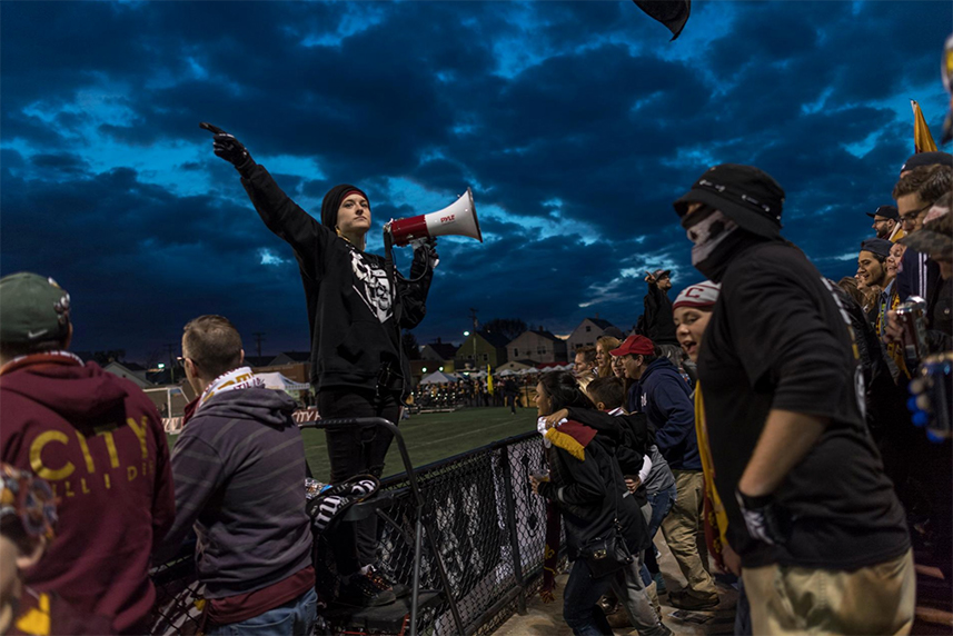 "Amanda Jaczkowski, 25, leads the crowd to cheer the Detroit City Football Club in a minor-league soccer game against the Dayton Dynamo Football Club. Born into a devoutly Catholic Polish-American family, she converted to Islam in her sophomore year of college. ""To be honest,"" she says, noting that she still listens to the same music and has the same best friend, ""I don't think I've changed that much."""