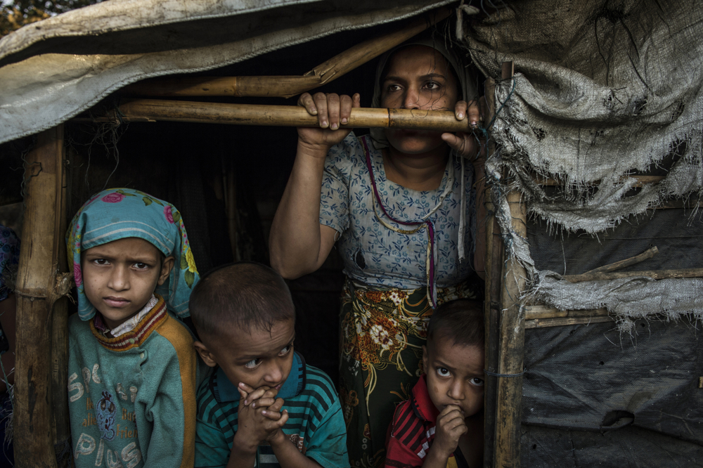 A Rohingya family, Burmese Muslims, live in the Thay Chaung camp for the Internally Displaced outside of Sittwe, which houses nearly 3000 people, November 23, 2015. The mother, pictured here, claimed all her children were malnourished, but because of the lack of medical professionals in the area, it was impossible to confirm.  An estimated one million stateless Rohingya have been stripped of their citizenship in Myanmar, and forced to live in modern-day concentration camps, surrounded by government military checkpoints.  They are not able to leave, to work outside the camps, do not have access to basic medical care, or food. Most aid groups are banned from entering or working in the camps, leaving the Rohingya to their own devices for sustenance and healthcare. Journalists are also routinely denied access to the Rohingya, Myanmar's way of ensuring the world doesn't see the slow, intentional demise of a population.