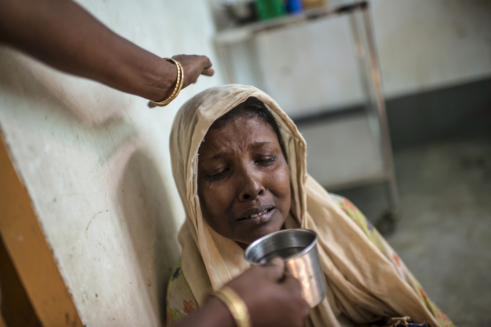 Moriam Katu, 50 years, who is gravely ill from severe asthma, is offered water as she struggles to breathe in the That Kay Pin Emergency Hospital in the camp for Internally Displaced Rohingya outside of Sittwe, in Myanmar, November 25, 2015.  Moriam was so ill, she could barely breathe, and began coughing up blood. She visited the emergency hospital at the That Kay Pin within the IDP camp, and there were not sufficient resources to treat her there. The medical advisor offered to transfer her to the government hospital in Sittwe, but she declined, because her family did not have enough money to keep her there. While her medical treatment would be free, her guardian would need to pay for food, which they estimated would be 20-30,000 for food for a week. She declined and went back home. A few days later, she returned, and was transferred to Sittwe hospital, and died 10 days later. An estimated one million stateless Rohingya have been stripped of their citizenship in Myanmar, and forced to live in modern-day concentration camps, surrounded by government military checkpoints.  They are not able to leave, to work outside the camps, do not have access to basic medical care, or food. Most aid groups are banned from entering or working in the camps, leaving the Rohingya to their own devices for sustenance and healthcare. Journalists are also routinely denied access to the Rohingya, Myanmar's way of ensuring the world doesn't see the slow, intentional demise of a population.