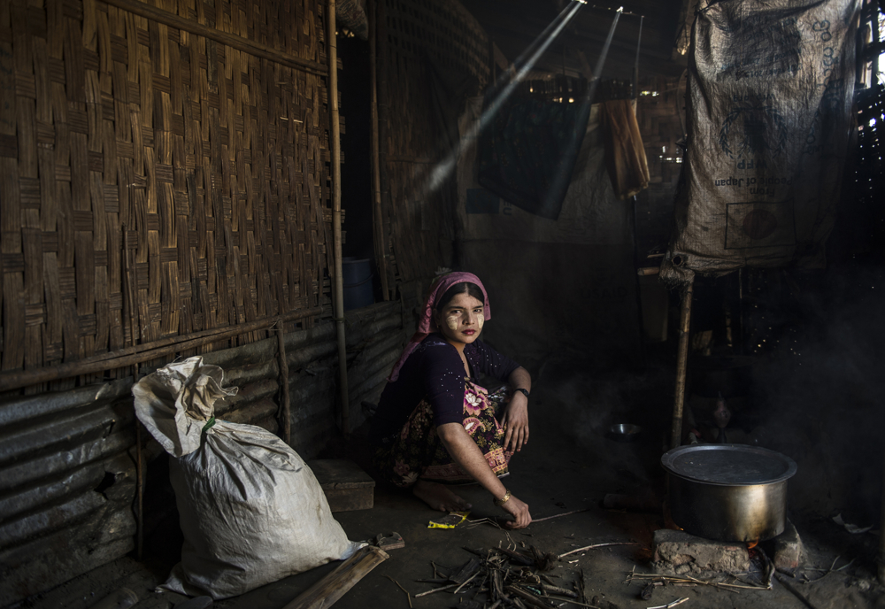 Aisha Begum, 18, cooks in her family home in the Say Tha Mar Gyi camp for Internally Displaced Rohingya, in Sittwe, Myanmar, November 26, 2015.  Aisha is married, but her husband left her less than a year ago to go live with his family again. An estimated one million stateless Rohingya have been stripped of their citizenship in Myanmar, and forced to live in modern-day concentration camps, surrounded by government military checkpoints.  They are not able to leave, to work outside the camps, do not have access to basic medical care, or food. Most aid groups are banned from entering or working in the camps, leaving the Rohingya to their own devices for sustenance and healthcare. Journalists are also routinely denied access to the Rohingya, Myanmar's way of ensuring the world doesn't see the slow, intentional demise of a population.