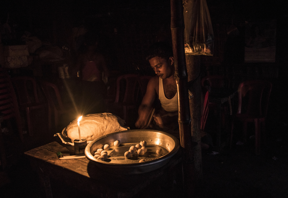 A Rohingya man, Burmese Muslims, sells food at a stall at night in the Thay Chaung camp for the Internally Displaced outside of Sittwe, which houses nearly 3000 people, November 23, 2015. There are limited opportunities for the Rohingya to work and make a living to support their families, as they are unable to travel outside the camps.  An estimated one million stateless Rohingya have been stripped of their citizenship in Myanmar, and forced to live in modern-day concentration camps, surrounded by government military checkpoints.  They are not able to leave, to work outside the camps, do not have access to basic medical care, or food. Most aid groups are banned from entering or working in the camps, leaving the Rohingya to their own devices for sustenance and healthcare. Journalists are also routinely denied access to the Rohingya, Myanmar's way of ensuring the world doesn't see the slow, intentional demise of a population.