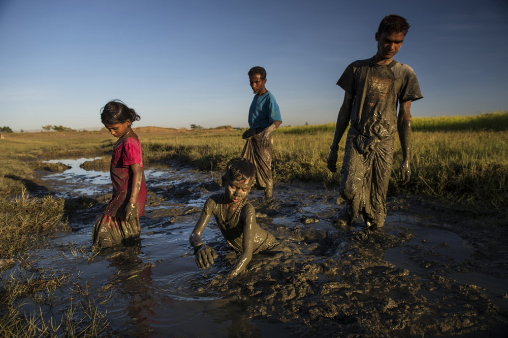 A Rohinga family, Burmese Muslims, look for small frogs to eat in the mud near their home in the camps for the Internally displaced in Sittwe,Myanmar, November 2015. The Rohingya have limited opportunities to work and support their families, and live in extreme poverty and marginalization.  An estimated one million stateless Rohingya have been stripped of their citizenship in Myanmar, and forced to live in modern-day concentration camps, surrounded by government military checkpoints.  They are not able to leave, to work outside the camps, do not have access to basic medical care, or food. Most aid groups are banned from entering or working in the camps, leaving the Rohingya to their own devices for sustenance and healthcare. Journalists are also routinely denied access to the Rohingya, Myanmar's way of ensuring the world doesn't see the slow, intentional demise of a population.