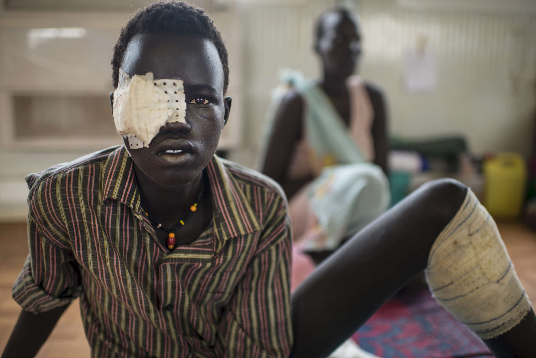 Lat Padang, who claims to be 18, a soldier with the opposition army, sits injured from battle while his mother sits in the background at a tent hospital at the base of the United Nations Mission in South Sudan in Bentiu, South Sudan, May 4, 2014.  Fighting between the government and the opposition has been going on since December 2013, and both sides are assumed to use child soldiers in combat despite international pressure and norms discouraging this.  Most combatants are careful not to admit to being under 18 because of potential backlash, so it is difficult to confirm based on appearances who is and who is not a child soldier.  Over twenty thousand internally displaced civilians live at the UNMISS base in Bentiu, and one million Southern Sudanese have been displaced from their homes as the civil war rages in the country, pitting ethnic Nu'er against Dinka.  (Credit: Lynsey Addario)