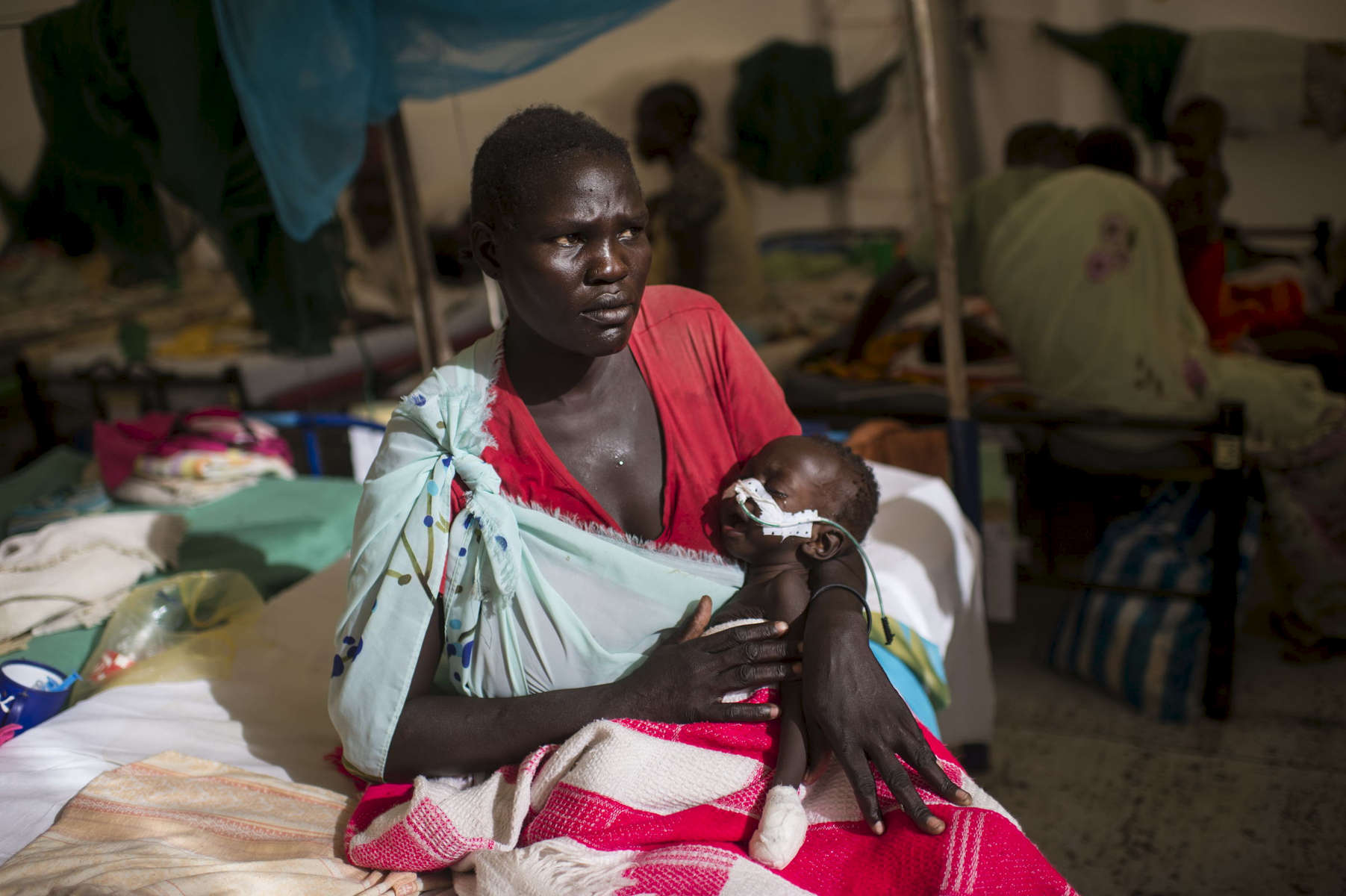 Nyakar Unwa, 34, holds her severely malnourished daughter, Monday, 6 months, who is being treated for malnutrition and additional complications at a tent hospital run by Doctors Without Borders at the base of the United Nations Mission in South Sudan base in Malakal, in the Upper Nile region, South Sudan, May 11, 2014. Nyakar, who has seven children, was displaced from her village of Owach during the civil war, and her family lost everything: their crops, cattle, and home.  They were forced to sell their clothes for food.  One million Southern Sudanese have been displaced from their homes since the start of the civil war in December 2013, pitting ethnic Nu'er against Dinka.  Because of continued fighting, many have been unable to plant crops to harvest the next season, and aid organizations have been unable to preposition food in anticipation of the rainy season.  According to the United Nations official coordinating humanitarian aid in South Sudan, if the civil war doesn't stop, and the country does not receive international aid, South Sudan will face the worst starvation in Africa since the 1980s, when hundreds of thousands of people died in Ethiopia's famine. (Credit: Lynsey Addario for The New York Times)