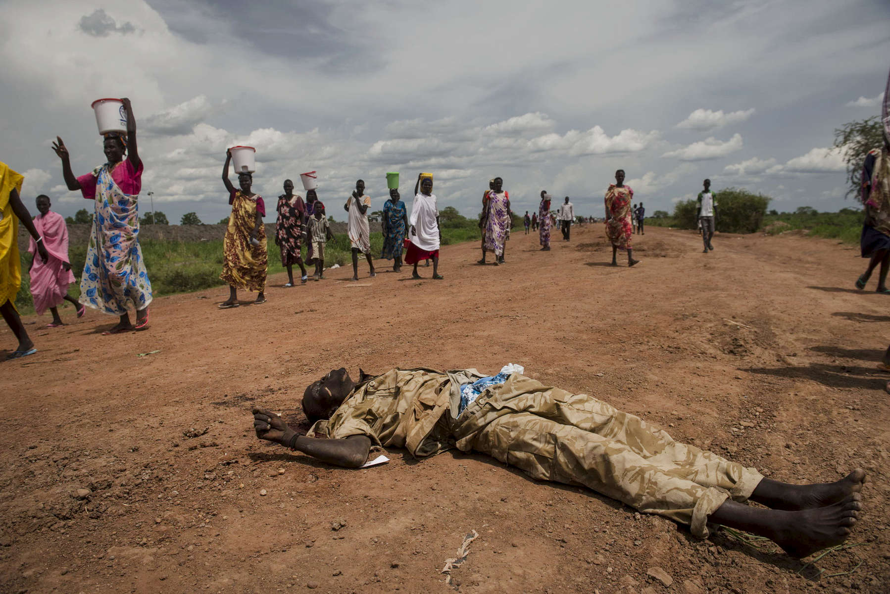 A dead government soldier with the Sudanese People's Liberation Army lies in the road in front of the base of the United Nations Mission in South Sudan as civilians pass by with water and food they collected from town during a lull in fighting between government and opposition forces in Bentiu, South Sudan, May 4, 2014.  Bentiu has changed hands between government and opposition control several times since the civil war began in December, and has been the scene of ethnic massacres where hundreds, if not thousands, have been killed in the past months, pushing over 20,000 into a camp for displaced inside the UNMISS camp outside the town.  One million Southern Sudanese have been displaced from their homes as the civil war rages in the country, pitting ethnic Nu'er against Dinka.  (Credit: Lynsey Addario)