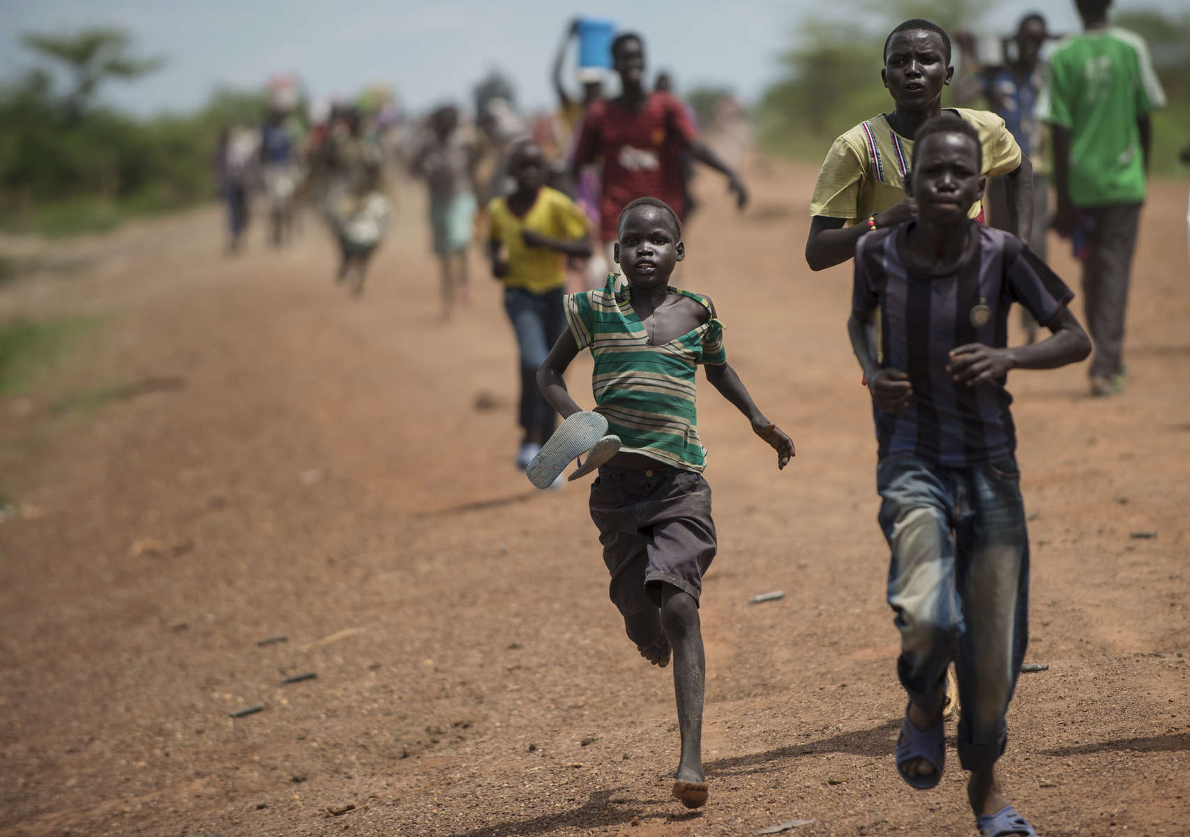 South Sudanese children and women run towards the camp for displaced at the United Nations Mission after fearing they saw a government troop in the bush as Soldiers with the Sudanese Peoples Liberation Army retreat from Bentiu following heavy battle with the opposition forces in South Sudan, May 5, 2014.  One million Southern Sudanese have been displaced from their homes as the civil war rages in the country, pitting ethnic Nu'er against Dinka.  (Credit: Lynsey Addario for The New York Times)