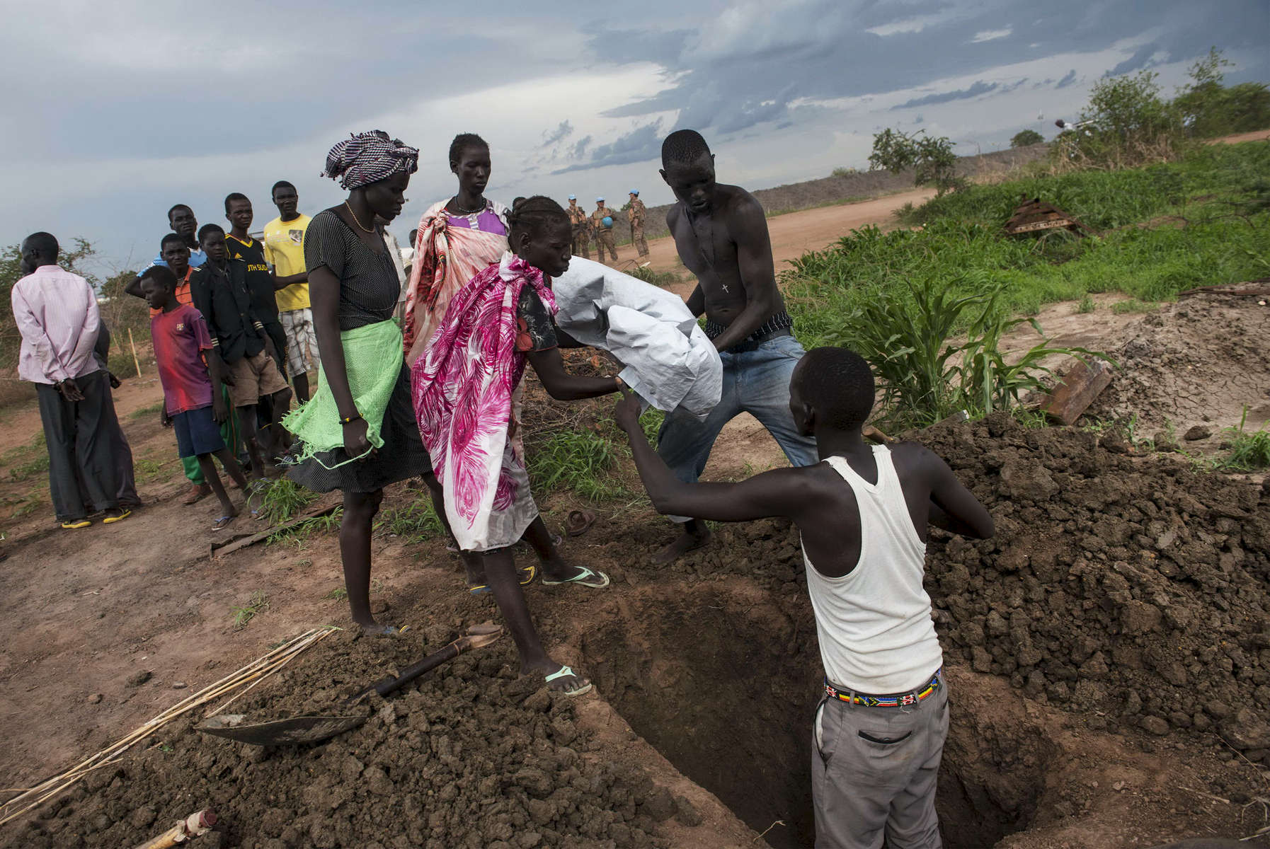 Relatives of Nyapes Lach, 4, carry her body to a freshly dug grave after she was shot in the head by crossfire while sitting in the camp for displaced at the United Nations Mission in South Sudan as fighting raged between government and opposition forces in Bentiu, South Sudan, May 4, 2014.  Bentiu has changed hands between government and opposition control several times since the civil war began in December, and has been the scene of ethnic massacres where hundreds, if not thousands, have been killed in the past months, pushing over 20,000 into a camp for displaced inside the UNMISS camp outside the town.  One million Southern Sudanese have been displaced from their homes as the civil war rages in the country, pitting ethnic Nu'er against Dinka.  (Credit: Lynsey Addario)