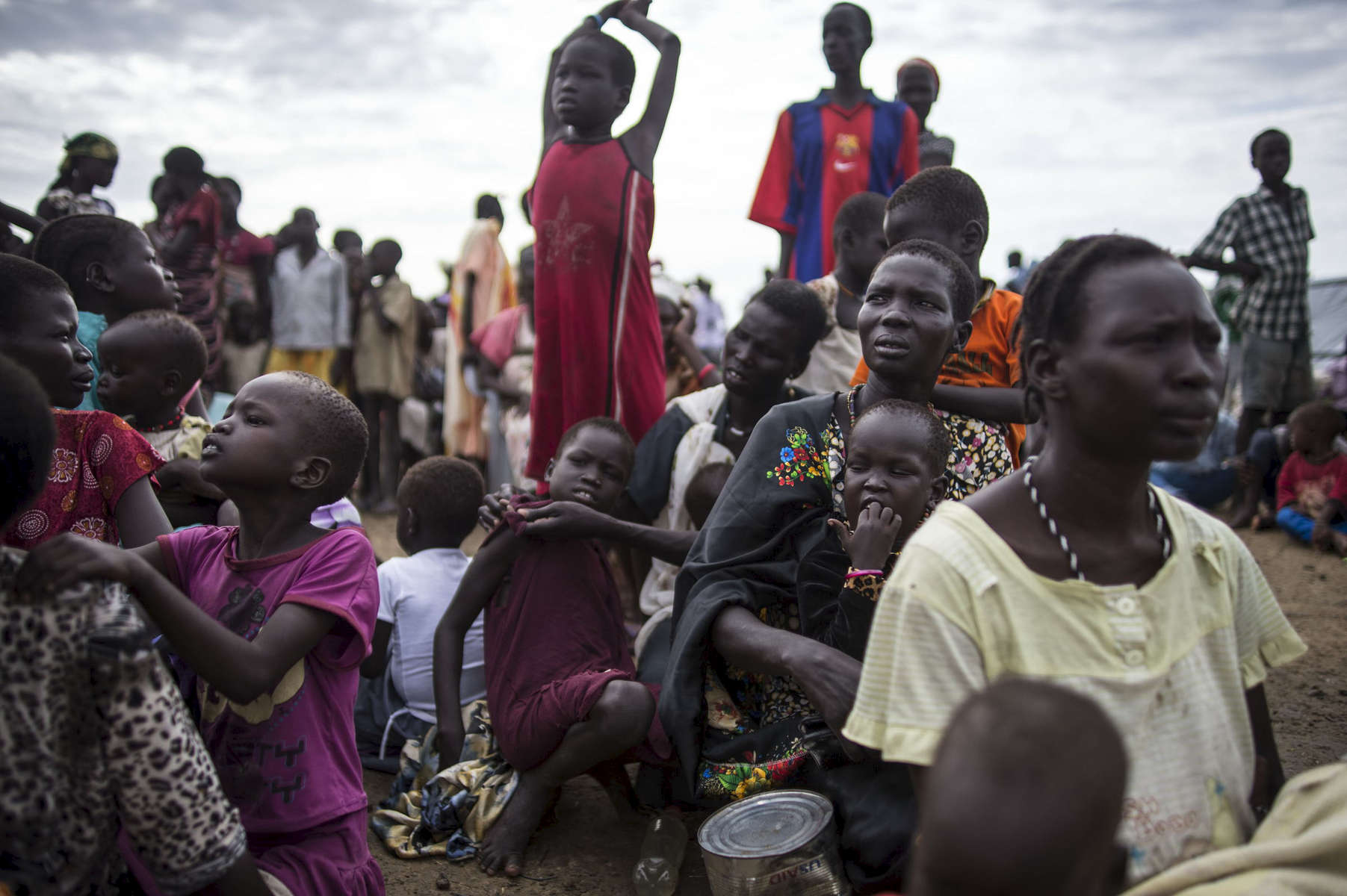 Internally displaced people wait to register for a food distribution at a camp at the base of the United Nations Mission in South Sudan in Bentiu, South Sudan, May 5, 2014.  Over twenty thousand internally displaced civlians live at the UNMISS base in Bentiu, and one million Southern Sudanese have been displaced from their homes across the country as the civil war rages in the country, pitting ethnic Nu'er against Dinka.  Many civilians have lost cattle, can not return to their farms to  plant crops to harvest the next season, and according to the United Nations official coordinating humanitarian aid in South Sudan, if the civil war doesn't stop, and the country does not receive international aid, South Sudan will face the worst starvation in Africa since the 1980s, when hundreds of thousands of people died in Ethiopia's famine. (Credit: Lynsey Addario)