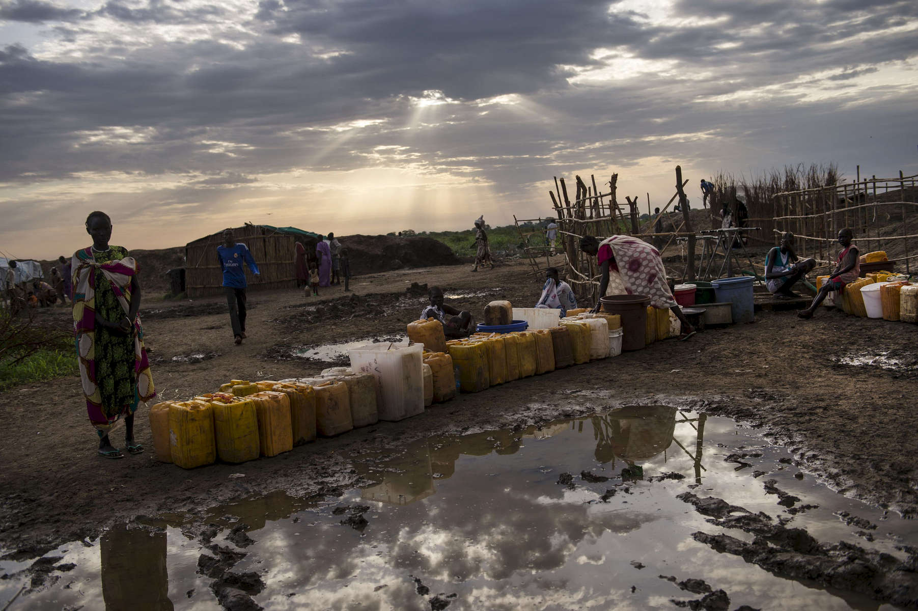 Internally displaced people wait for a water at dawn at the base of the United Nations Mission in South Sudan in Bentiu, South Sudan, May 4, 2014.  IDPs living at the UNMISS camp in Bentiu face a limited supply of water, and are living in highly unsanitary conditions, where raw sewage flows openly throughout the camp, and children have high rates of diarrhea and skin ailments frequently caused by exposure to tainted water. Over twenty thousand IDPs live at the UNMISS base in Bentiu, and one million Southern Sudanese have been displaced from their homes as the civil war rages in the country, pitting ethnic Nu'er against Dinka.  The United Nations has scrambled to provide unprecedented safe havens for civilians inside their camps, but funding to provide for this emergency situation has been limited.  (Credit: Lynsey Addario)